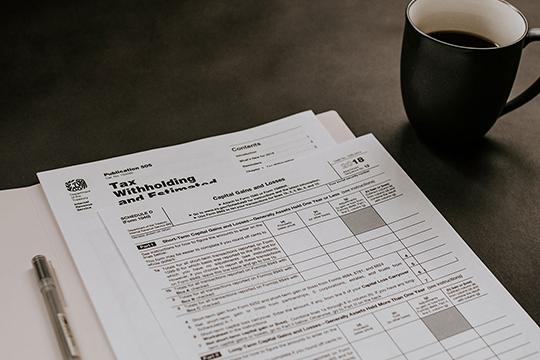Tax Documents and coffee cup on top of desk